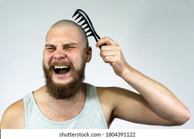 Portrait of cry bearded bald man holding a brush in his hand. The concept of hair loss and hair transplantation