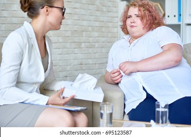 Portrait of crying obese woman opening up to female psychiatrist during therapy session  on mental issues in doctors office