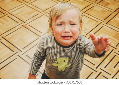 Portrait of crying toddler pulling hands to the mother