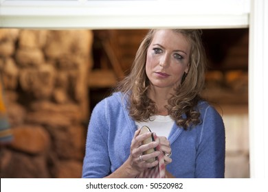 Portrait of a crying woman drying a dish and staring into the distance as mascara runs down her face. Horizontal format.
