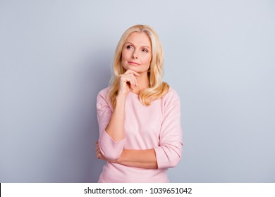Portrait of cunning curious emotion expressing pretty charming candid with long wavy curly haircut pensive granny planning weekend vacation holiday wearing casual pullover isolated on gray background