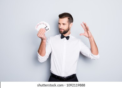 Portrait of cunning foxy magician with modern hairstyle and stubble in white shirt with bowtie holding set of cards in hand, making trick, focus, isolated on grey background