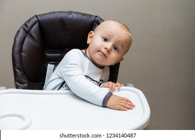 A portrait of curious adorable baby boy of one year old sitting in the highchair not fastened, leaning to the side and looking at the camera with interest wearing pyjama and amber teething necklace.
