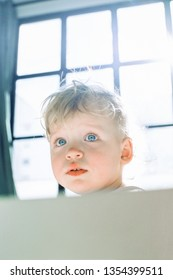 Portrait of a curious baby girl at the window