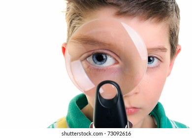 Portrait of a curious boy looking through the magnifying glass