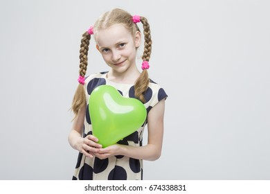 Portrait of Curious Funny Caucasian Blond Girl With Pigtails Posing in Polka Dot Dress Against White. Holding Green Air Balloon. Horizontal Image