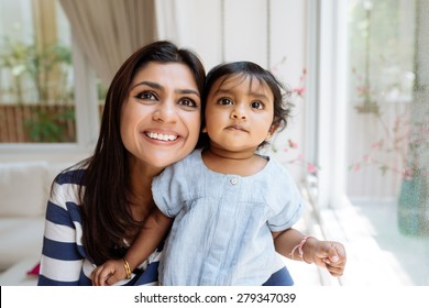 Portrait of curious little girl and her smiling mother looking up