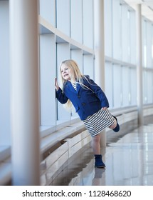 Portrait of curious little girl looking at window in mall