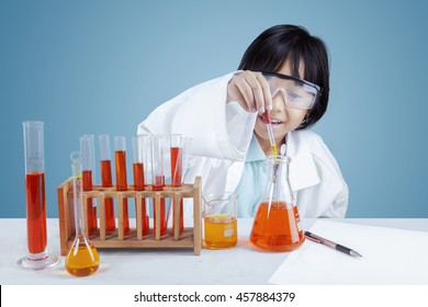 Portrait of a curious little girl making chemical research with chemistry liquid in test tubes