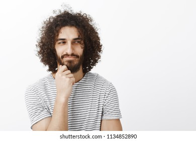 Portrait of curious playful handsome male with curly hair, looking aside and smirking, holding hand on beard while thinking and having great plan, wanting to say hi to cute girl in cafe over gray wall