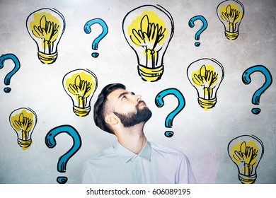 Portrait of curious young man on concrete background with drawn lamps and blue question marks. Solution concept
