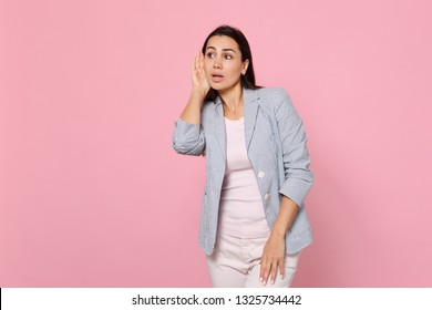 Portrait of curious young woman in striped jacket eavesdrop with hearing gesture, looking aside isolated on pink pastel wall background. People sincere emotions, lifestyle concept. Mock up copy space