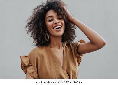 Portrait von geschmeidig gebrannter afrikanischer, dunkelhäutiger Frau auf beigem, oberem, lächelndem und ruffelndem Haar auf einzeln grauem Hintergrund.
