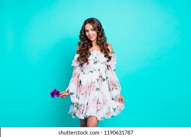 Portrait of curly brunette hold small purple bouquet of flowers in hand and look at camera hold summer dress isolated on bright turquoise background