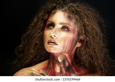 portrait of curly girl with art conceptual makeup and dark background