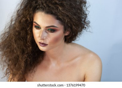 portrait of a curly girl on a background with green shadows on the eyelids