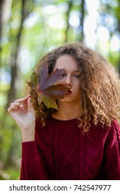 Portrait of curly hair teen girl holding maple leaf in autumn forest