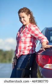 Portrait of curly hair woman with own car over blue sky