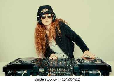 Portrait of curly hair young DJ playing music on light background