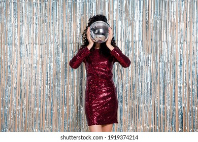 Portrait of curly hairstyle person hands hold disco ball covering face head isolated on shiny decorated curtain