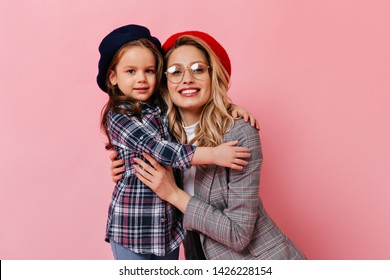 Portrait of curly mom and daughter in checkered jackets on pink background. Adult woman in glasses hugs little girl in beret