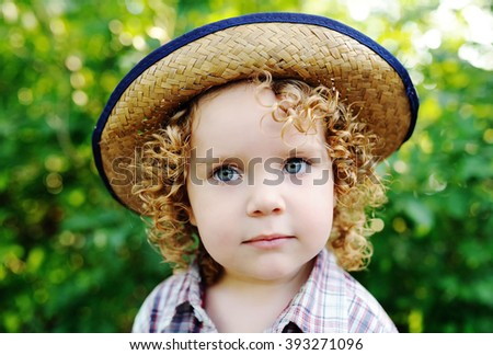 72d96c17f51 portrait of curly red-haired baby in a hat. Cute baby girl cowboy.