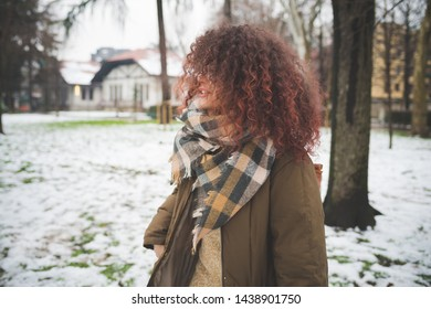 portrait of curly woman standing outdoor in winter day – exploration, youth culture, movement