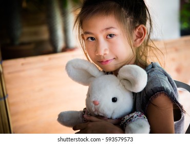 Portrait of cut little girl and rabbit dall sitting in room,Happy girl