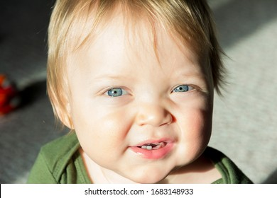 Portrait of a cute 10 month old baby boy with blond hair blue eyes and first teeth