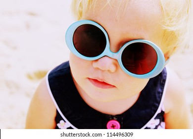 Portrait of cute 1,5 years old baby with fashin vintage sunglasses. sunglasses worn on the contrary