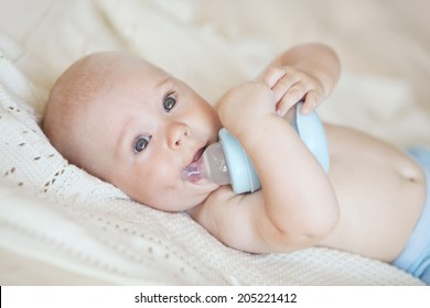 Portrait of a cute 4 months baby drinking water from a bottle