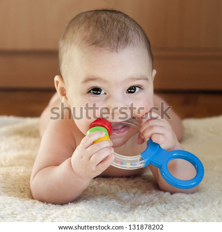 Portrait of a cute 6 month old baby, boy or girl, playing with teething toy. - Image Cute Month Old Baby Stock Photo (Edit Now) 131878202