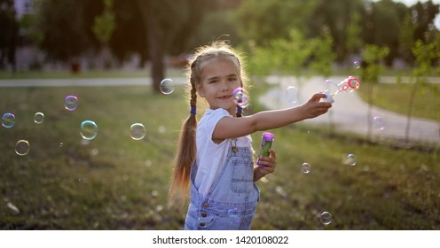 Portrait of cute 6-7 preschool girl with two braids blowing soap bubbles in the park at summer, happy childhood concept, emotional outdoor lifestyle, banner format