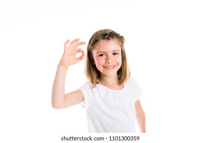 Portrait of a cute 7 years old girl Isolated over white background show positive hand