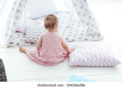 Portrait of cute adorable caucasian baby girl sitting on floor back to camera, near pillow and bed