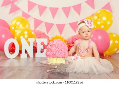 Portrait of cute adorable Caucasian baby girl in tutu tulle skirt celebrating her first birthday. Cake smash concept. Child kid sitting on floor in studio with pink flags and balloons, eating  dessert