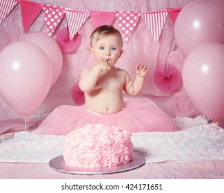 Portrait of cute adorable Caucasian baby girl with blue eyes in pink tutu skirt celebrating her first birthday with gourmet cake and balloons looking in camera, cake smash first year concept