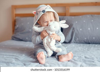 Portrait of cute adorable Caucasian blonde smiling baby girl with blue eyes in grey pajama with fox cat animal hood sitting on bed in bedroom and holding toy. Happy childhood lifestyle concept