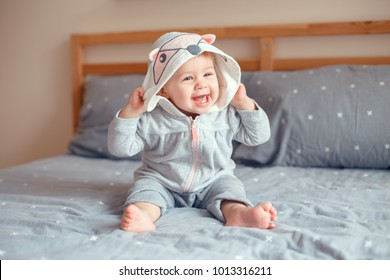 Portrait of cute adorable Caucasian blonde smiling baby girl with blue eyes in grey pajama with fox cat animal hood sitting on bed in bedroom. Natural emotion face expression.
