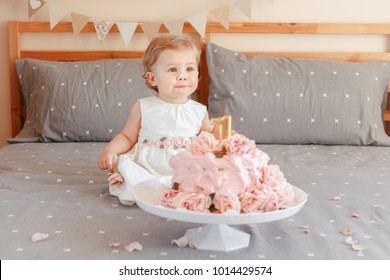 Portrait of cute adorable Caucasian blonde baby girl in white dress celebrating her first birthday. Home indoors cake smash first year concept