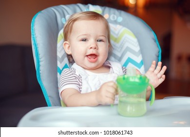 Portrait of cute adorable Caucasian child kid girl sitting in high chair drinking water from spill-proof sippy cup. Everyday lifestyle. Candid real authentic moment