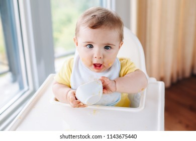 5e9e1ddec836 Portrait of cute adorable Caucasian child boy with dirty messy face sitting  in high chair eating