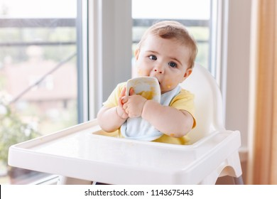 Portrait of cute adorable Caucasian child boy with dirty messy face sitting in high chair eating apple puree with fingers. Everyday home childhood lifestyle. Infant trying supplementary baby food