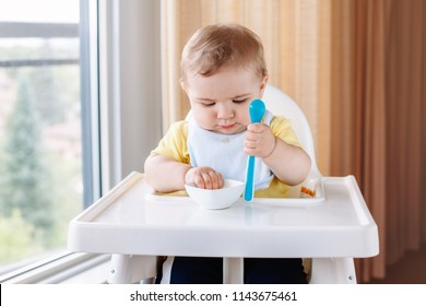 Portrait of cute adorable Caucasian child boy with dirty messy face sitting in high chair eating apple puree with spoon. Everyday home childhood lifestyle. Infant trying supplementary baby food