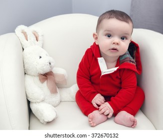 Portrait of cute adorable Caucasian smiling baby boy girl with black brown eyes in red hoodie shirt sitting in chair with toy looking directly in camera