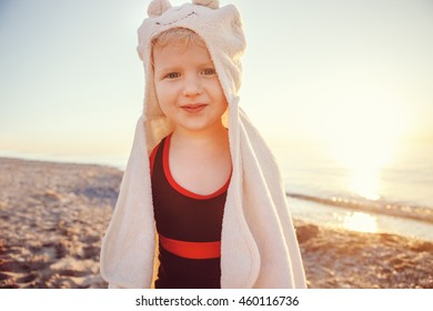 Portrait of cute adorable funny happy smiling toddler little girl with towel on beach making poses faces having fun, emotional face expression, lifestyle sunset summer mood, toned