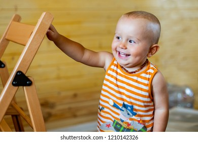 A portrait of a cute adorable laughing happy baby boy of 12 months or 1 year old looking aside wearing amber teething baby necklace in a sleeveless striped orange top holding the back of the chair.
