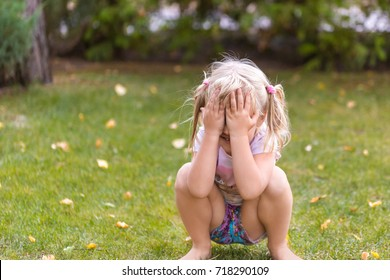 Portrait of cute adorable little blonde caucasian girl squatting on green grass lawn outdoors, having fun and playing hide and seek game, hiding the face with hands. Happy childhood concept.