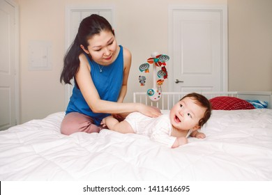 Portrait of cute adorable mixed race Asian mother with newborn baby doing massage and physical exercises. Early development and health care lifestyle concept