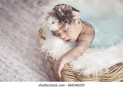 portrait of cute and adorable newborn baby with head band sleeping in basket.New life and parenting concept.